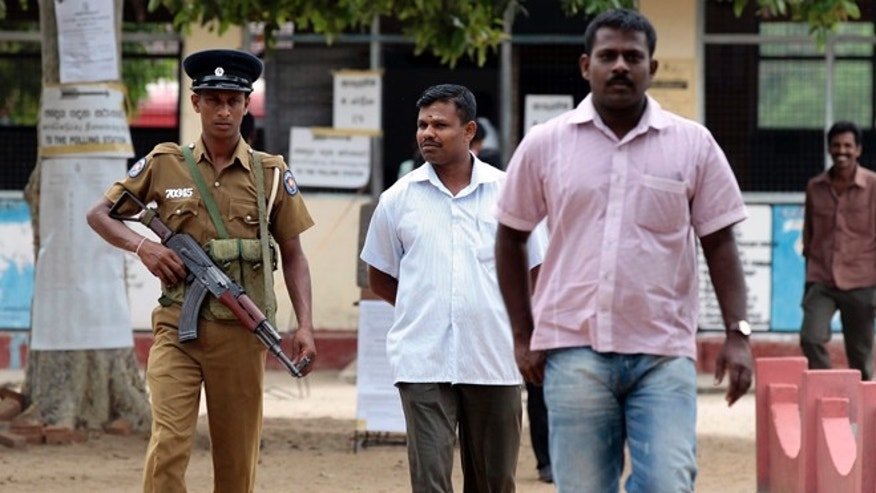 Sept. 8, 2012: A Sri Lankan police officer stands guard as ethnic Tamil voters leave a polling station after casting their votes in Batticaloa, Sri Lanka.