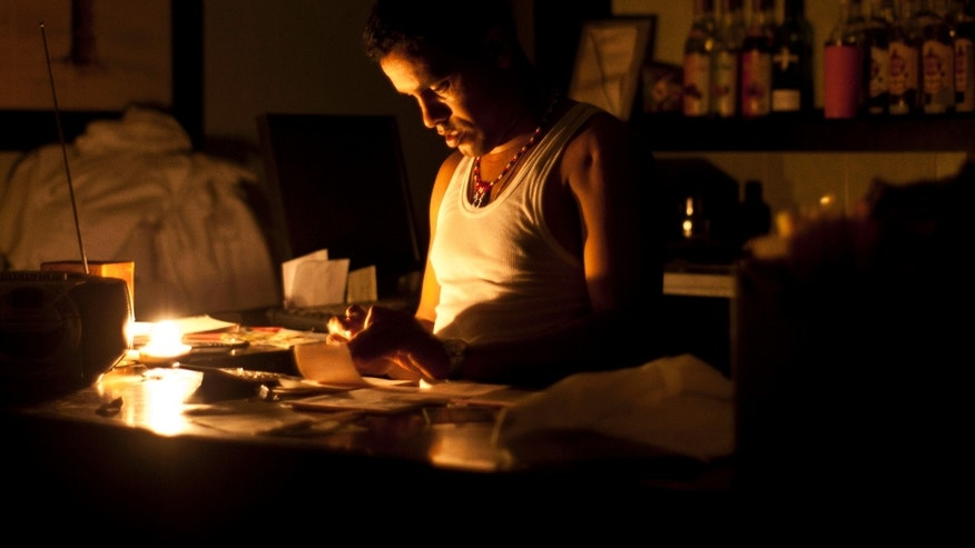 Sept 9, 2012 - A bartender works on accounts by candle light  during the blackout in Havana, Cuba.