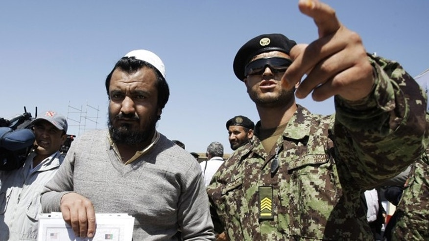 Sept. 10, 2012: An Afghan soldier, right, escorts a released prisoner, Mohammad Karim, following a hand over ceremony of U.S.- run prison to Afghan government in Bagram north of Kabul, Afghanistan.