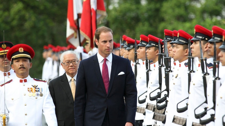 Prince William, the Duke of Cambridge, center, is accompanied by Singapore's President Tony Tan, as he inspects an honor guard during the welcome ceremony at the Istana, or Presidential Palace, on Tuesday Sept. 11, 2012 in Singapore. The Duke and Duchess of Cambridge started an official three-day trip to Singapore Tuesday. (AP Photo/Wong Maye-E)