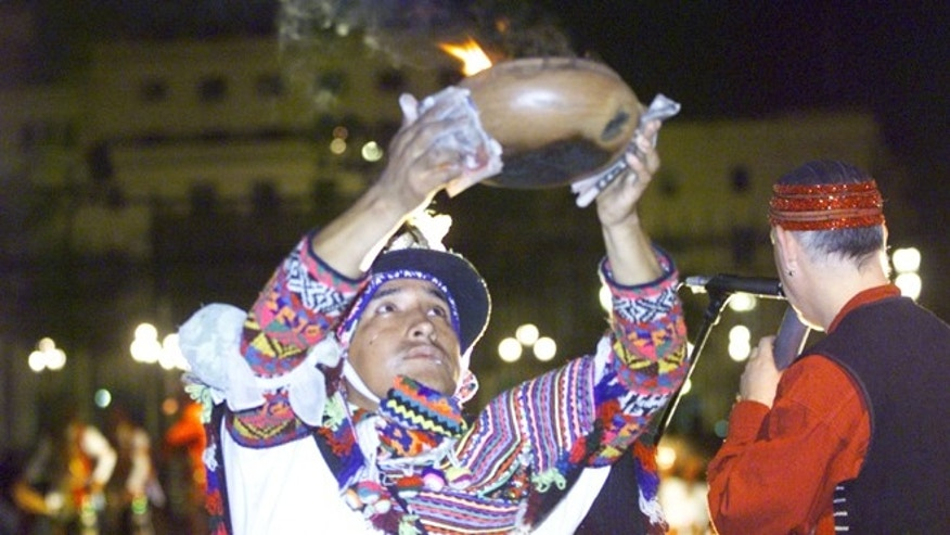 A Peruvian Shaman performs a ritual offering which pays homage to the land November 23, 2001 at the entrance of the presidential palace in Lima, Peru. (Photo by Getty Images)