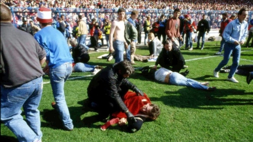FILE - In this April 15, 1989 file photo, showing police, stewards and supporters as they tend to wounded soccer supporters on the field at Hillsborough Stadium, in Sheffield, England. 96 Liverpool fans were crushed to death in the incident at the FA Cup semi-final match Liverpool against Nottingham Forest.