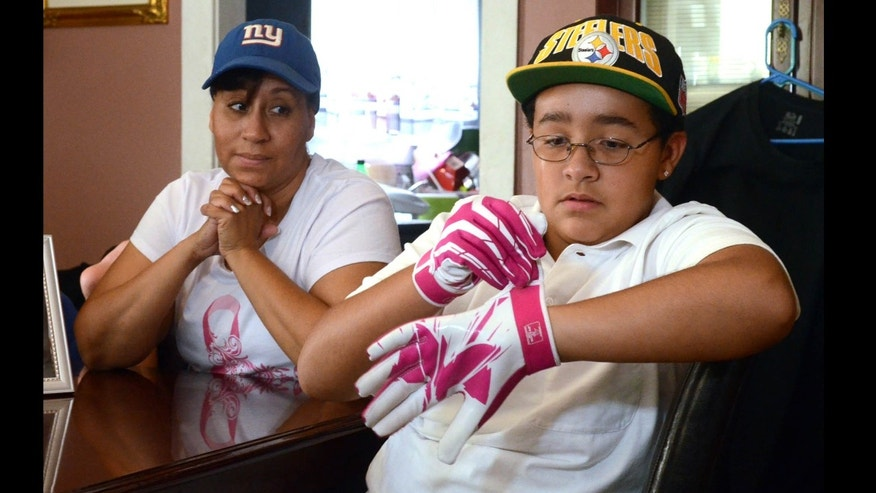 Julian Connerton wears his pink football gloves that he bought in honor of his mom Mayra Cruz-Connerton, who has breast cancer, at their home in Egg Harbor City, N.J. Photo/The Press of Atlantic City, Danny Drake)