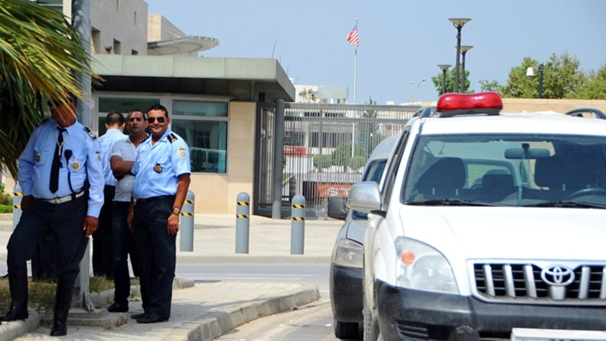 Sept. 12, 2012: Police officers guard the United States embassy in Tunis, as ultraconservative Muslims demonstrate outside the embassy to demand the closure of the embassy and the departure of the ambassador.