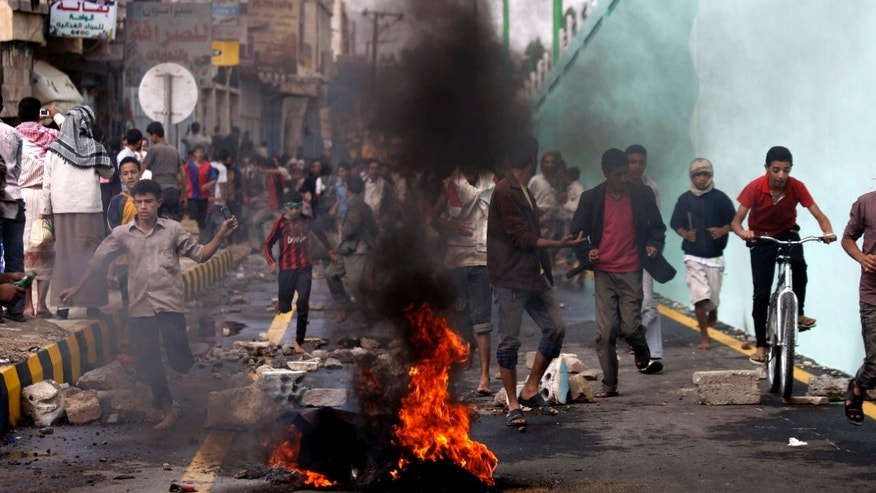 Sept. 13, 2012: Protesters run as police, unseen, open fire into the air near the U.S. Embassy during a protest about a film ridiculing Islam's Prophet Muhammad, in Sanaa, Yemen. Yemen's president has apologized to President Barack Obama for the attack on the U.S. Embassy in Sanaa, the Yemeni capital, by a mob angry over an anti-Islam film.