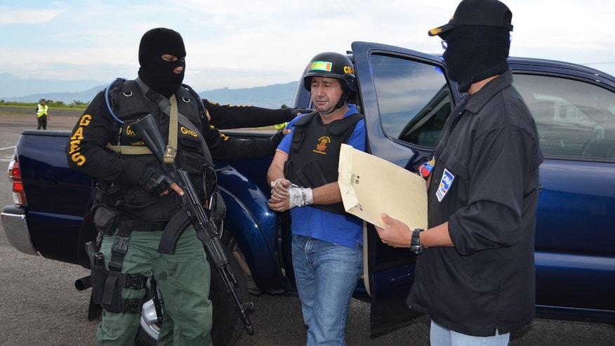 Sept. 19, 2012: Venezuela's judicial police officers escort alleged Colombian drug trafficker Daniel Barrera, center, at the Regional Command No. 1 National Guard base in San Cristobal, Tachira state, Venezuela.