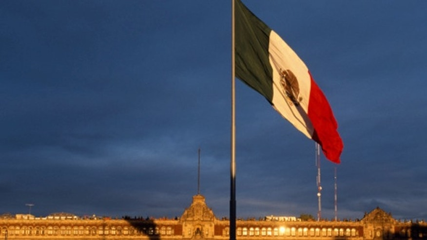 Mexico, Mexico City. Giant Mexican flag in the Zocala Squarewith the National Palace behind.