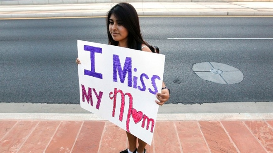 "Cynthia Diaz, 17, quietly holds up a sign telling her story of her Mom's deportation last year, as she joins dozens who rally in front of  U.S. Immigration and Customs Enforcement building, a day after a portion of Arizona's immigration law took effect, Wednesday, Sept. 19, 2012, in Phoenix. Civil rights activists contend will lead to systematic racial profiling, as the protesters chanted ""No papers, no fear."" (AP Photo/Ross D. Franklin)"