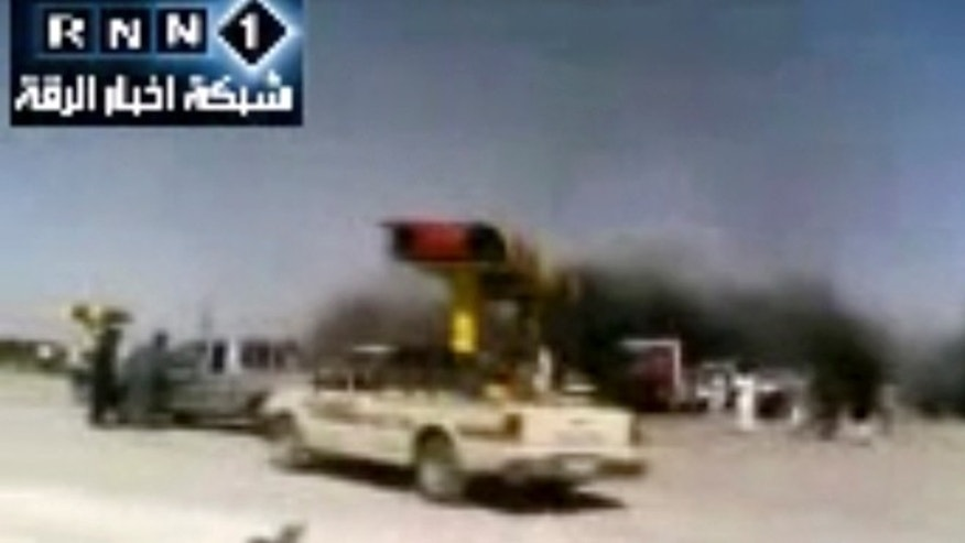In this image taken from video obtained Thursday, Sept. 20, 2012 from the Ugarit News, which has been authenticated based on its contents and other AP reporting, people are seen after an airstrike on a gas station in Raqqa, Syria.