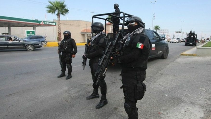 Sept. 18, 2012: Rapid response Coahuila state police stand at a checkpoint in the city of Piedras Negras, Mexico. Federal police units and Mexican troops, including 70 members of an elite military special forces unit, are searching for inmates who fled the prison in this city across the border from Eagle Pass, Texas.