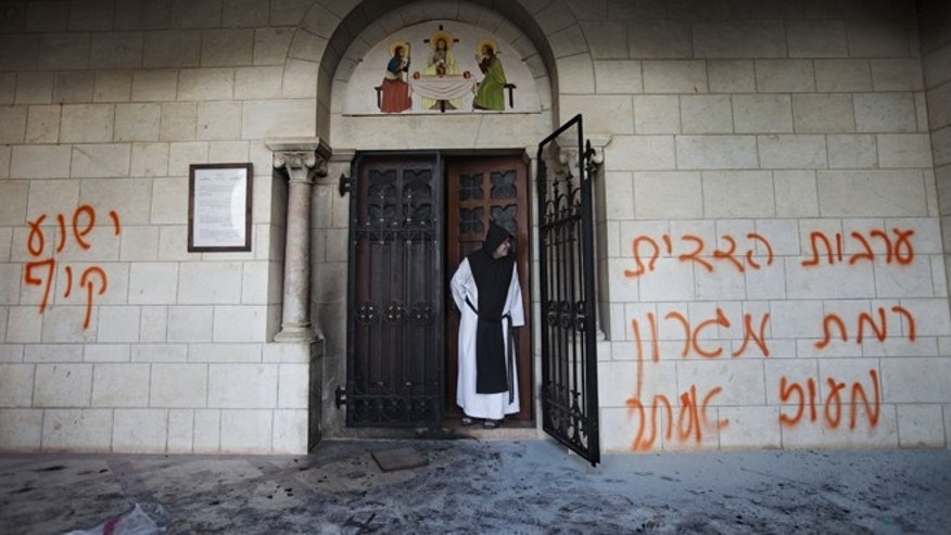Sept. 4, 2012: A Catholic monk stands in a doorway of the Latrun Trappist Monastery where Israeli police say vandals spray-painted anti-Christian and pro-settler graffiti and set the monastery&#39&#x3b;s door on fire, in Latrun, between Jerusalem and Tel Aviv, Israel.