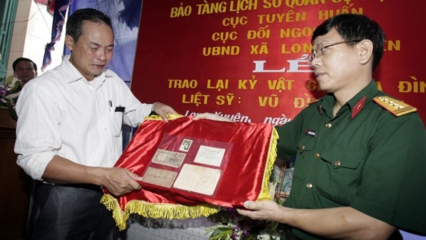 Sept. 21, 2012: Vu Dinh Son, left, cries as he is given a diary and other mementos of his father by army officer Nguyen Xuan Nang in northern province of Hai Duong, Vietnam.