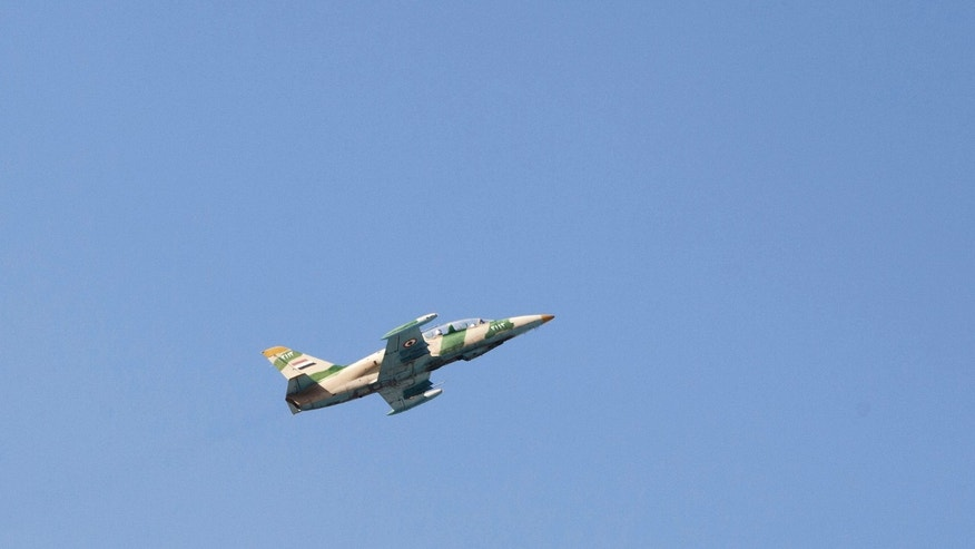 Sept. 23, 2012: In this photo, a Syrian army jet is seen after attacking a residential area near the Dar al Shifa hospital in Aleppo, Syria.
