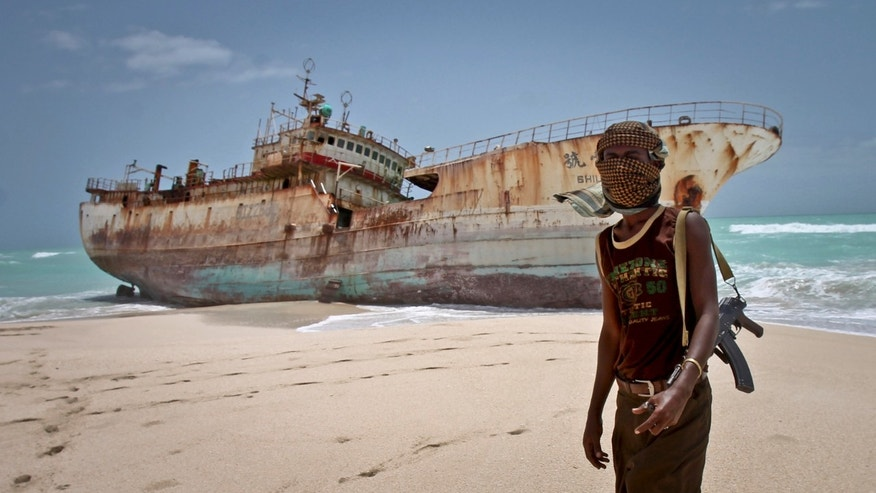 Sept. 23, 2012: Masked Somali pirate Abdi Ali stands near a Taiwanese fishing vessel that washed up on shore after the pirates were paid a ransom and released the crew, in the once-bustling pirate den of Hobyo, Somalia.