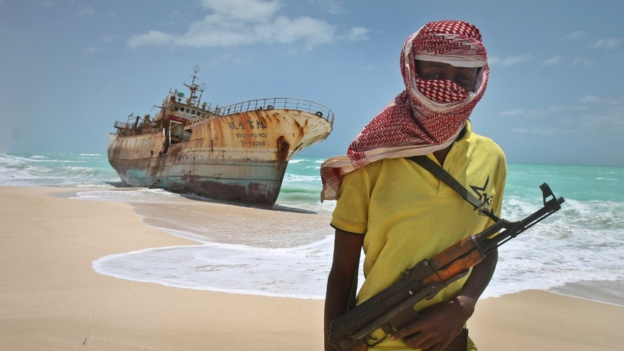 Sept. 23, 2012: Masked Somali pirate Hassan stands near a Taiwanese fishing vessel that washed up on shore after the pirates were paid a ransom and released the crew, in the once-bustling pirate den of Hobyo, Somalia.
