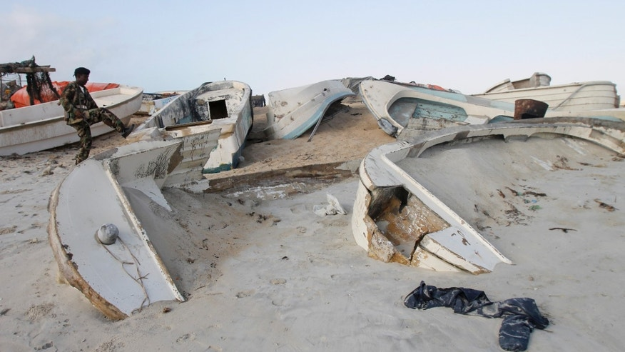 Sept. 23, 2012: Somali government soldier walks next to some of the overturned pirate skiffs that litter the dunes on the shoreline near the once-bustling pirate den of Hobyo, Somalia.