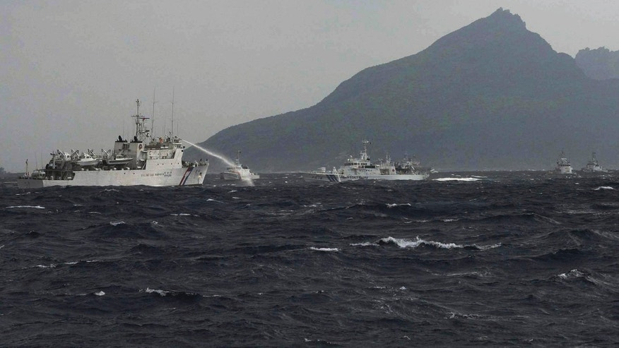 Sept. 25, 2012: In this photo released by Taiwan's Central News Agency, a Taiwan Coast Guard patrol boat, left, sprays its water cannon towards a Japan Coast Guard patrol boat off the disputed islands called Senkaku in Japan and Diaoyu in China, in the East China Sea.
