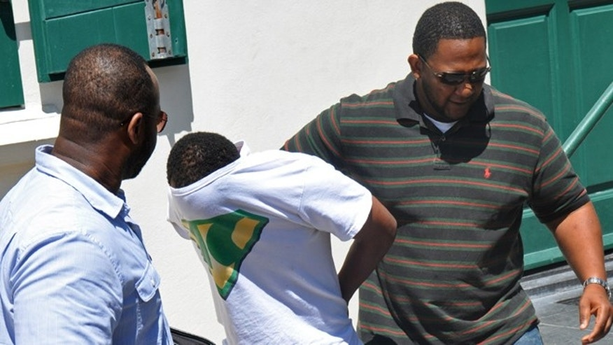 With his T-shirt pulled over his head, Jamaican Meyshane Johnson, center, a suspect in the slaying of a South Carolina couple, is escorted by police officers outside the court building after his arraignment in Philipsburg, St. Maarten.