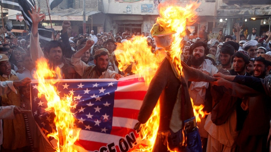 FILE - In this Thursday, Sept. 20, 2012 file photo, Pakistani protesters burn a representation of a U.S. flag and an effigy of U.S. President Barack Obama in the Pakistani border town of Chaman along the Afghanistan border. U.S.-funded ads on Pakistani television include President Barack Obama extolling Americas religious tolerance. To many in the Muslim world, this misses the mark in efforts to calm the outrage over a film mocking the Prophet Muhammad. (AP Photo/Matiullah Achakzai, File)