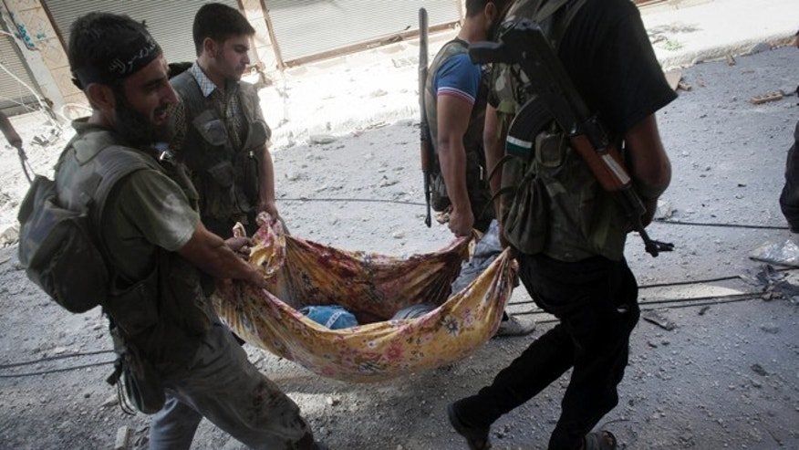 Sept. 26, 2012: Free Syrian Army fighter carry the body of their comrade away from the front line during clashes against Syrian Army in Aleppo, Syria.