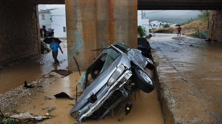 Sept. 28, 2012 - Residents walk by a wrecked car carried away by flash floods after heavy rain in the town of Villanueva del Rosario, Malaga, southern Spain.