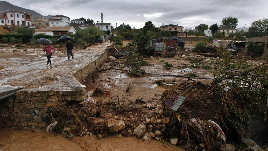 Sept. 28, 2012 - residents walk on a muddy street after heavy rain caused flash floods in the town of Villanueva del Rosario, Malaga, southern Spain.