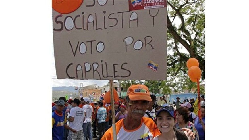 "In this Sept. 1, 2012 photo, a man and his daughter pose with a poster that reads in Spanish; ""I'm a socialist and will vote for Capriles,"" at a campaign rally in Miranda, Venezuela. From single mothers to construction workers, a segment of President Hugo Chavez supporters have been turning away from the president and instead considering new leadership. They've become key to the Oct. 7 presidential vote and to opposition presidential candidate Henrique Capriles' strategy. (AP Photo/Fernando Llano)"