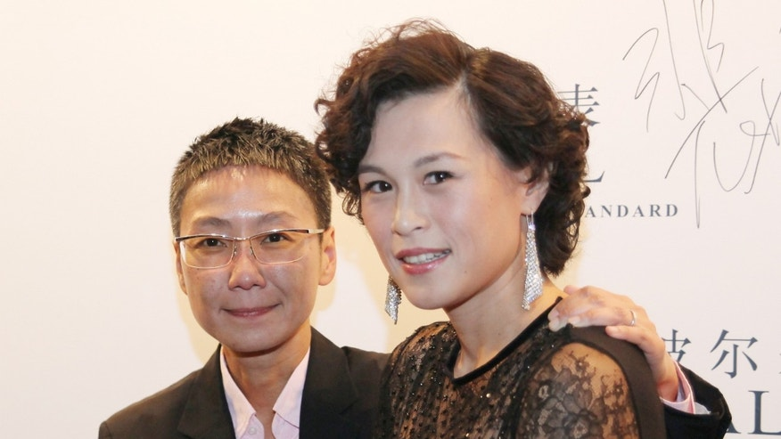 Undated photo, Gigi Chao, right, daughter of the Hong Kong property tycoon Cecil Chao, poses with her partner Sean Eav at an event in Hong Kong.