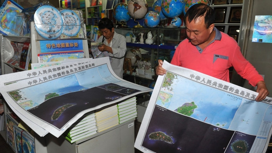 Sept. 19, 2012: In this photo, a costumer picks copies of newly-published maps of disputed islands, called Diaoyu in China and Senkaku in Japan, at a state-owned book store in Beijing, China.