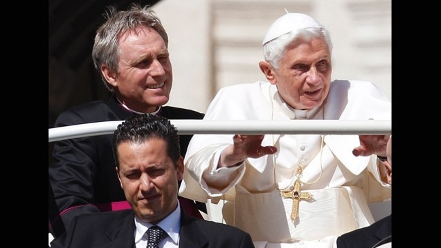 In this file photo taken Wednesday, May 2, 2012, Pope Benedict XVI arrives in St. Peter's square at the Vatican for a general audience as his then-butler Paolo Gabriele, bottom, and his personal secretary Georg Gaenswein sit in the car with him.