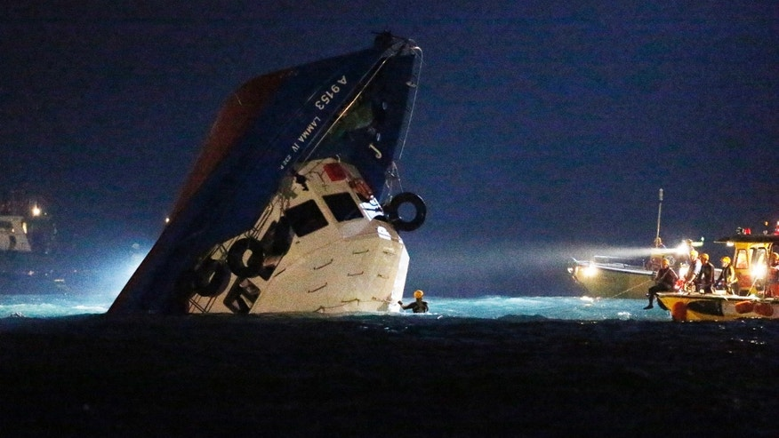 Oct. 2, 2012 - Rescuers check on a half submerged boat after it collided Monday night near Lamma Island, off the southwestern coast of Hong Kong Island.