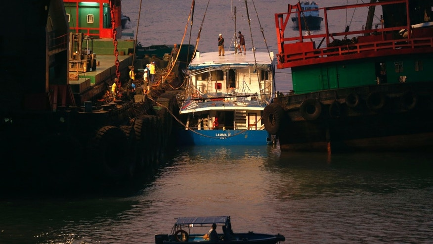 Oct. 2, 2012: Workers check on a salvaged boat which sank previous night after colliding with a ferry near Lamma Island, off the southwestern coast of Hong Kong Island.