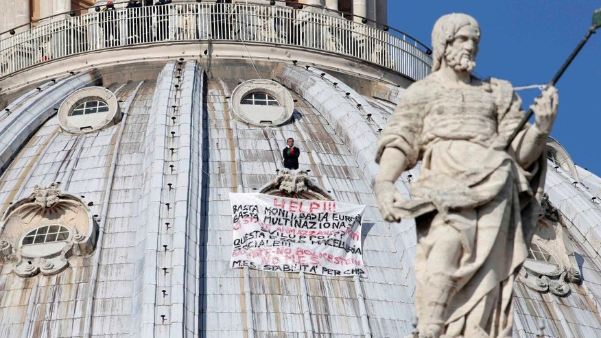 "Oct. 3, 2012: Firefighters look at Italian businessman Marcello di Finizio standing above his banner  which reads in Italian ""Help!! Enough Monti (Italian Premier Mario Monti), enough Europe, enough multinationals, you are killing all of us. Development?? This is a social butchery!!"", as he protests on St. Peter's 42-feet-high dome, at the Vatican."