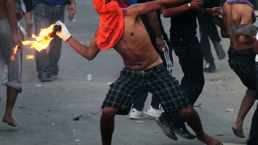 Oct. 3, 2012 - A Bahraini anti-government protester throws a petrol bomb toward riot police, unseen, firing tear gas and stun grenades in Sadad, Bahrain.