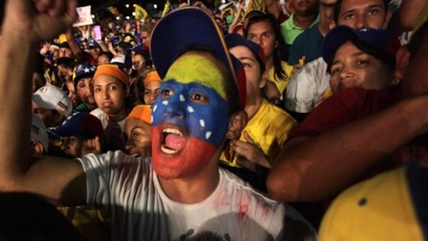 Supporters of opposition presidential candidate Henrique Capriles, one with his face painted with the colors of the Venezuelan flag, cheer during his closing campaign rally in Barquisimeto, Venezuela, Thursday, Oct. 4, 2012. Capriles will run against President Hugo Chavez in the presidential elections Oct. 7. (AP Photo/Fernando Llano)