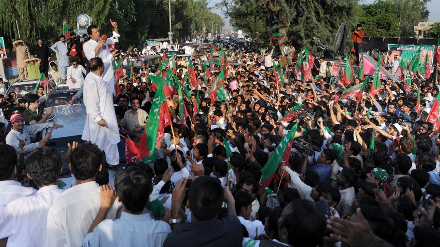 Oct. 6, 2012: Pakistan's ex-cricket star-turned-politician Imran Khan, top left, addresses supporters during a peace march in Mianwali, Pakistan.