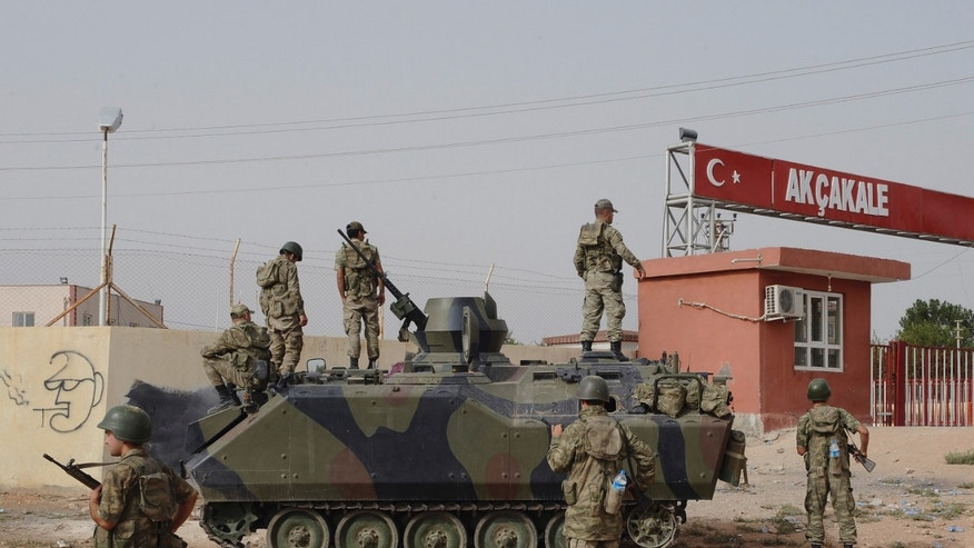 Turkish military station at the border gate with Syria, across from Syrian rebel-controlled Tel Abyad town, in Akcakale, Turkey, Sunday, Oct. 7, 2012. (AP Photo)