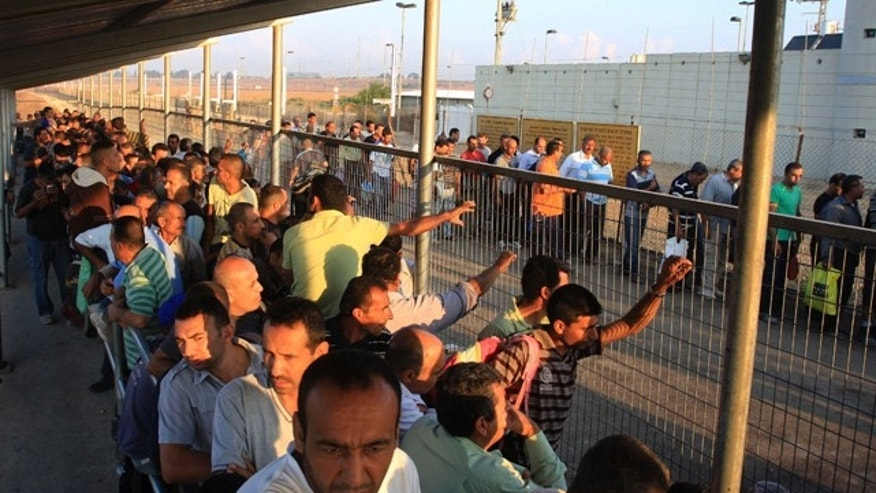 Oct. 9, 2012: Palestinian workers wait to cross to Israel at the Qalqiliya checkpoint. In response to an economic crisis gripping the West Bank, Israel has suddenly increased the number of permits for Palestinians to work inside Israel. (AP)