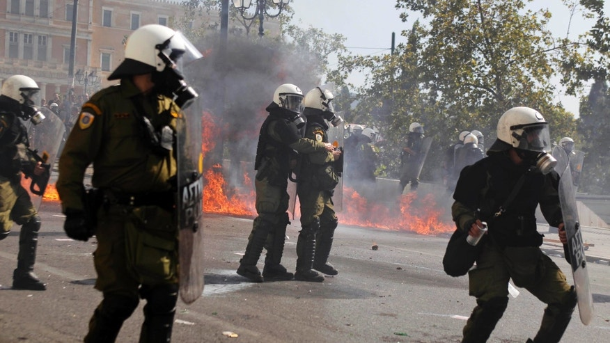 Riot police try to avoid petrol bombs thrown by protesters during clashes during the 24-hour nationwide general strike on Thursday, Oct. 18, 2012. Hundreds of youths pelted riot police with petrol bombs, bottles and chunks of marble Thursday as yet another Greek anti-austerity demonstration descended into violence. (AP Photo/Petros Giannakouris)