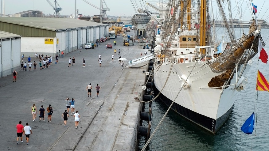 The crew of the flagship of Argentin's navy, the A.R.A. Libertad, run along the dock at the port of Tema, outside Accra, Ghana, Thursday, Oct 11, 2012, where the Libertad is being held.