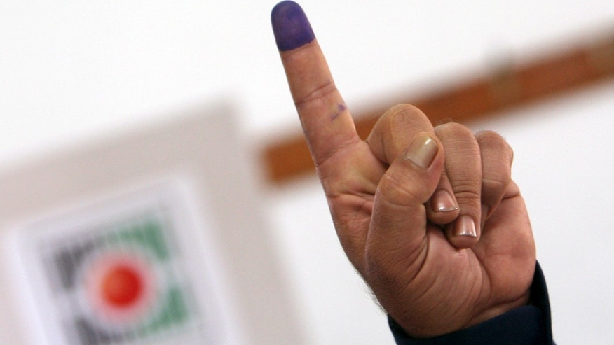 Oct. 18, 2012 - A Palestinian police officer shows his ink-stained finger after casting an early vote during local elections at a polling station in the West Bank town of Jenin.