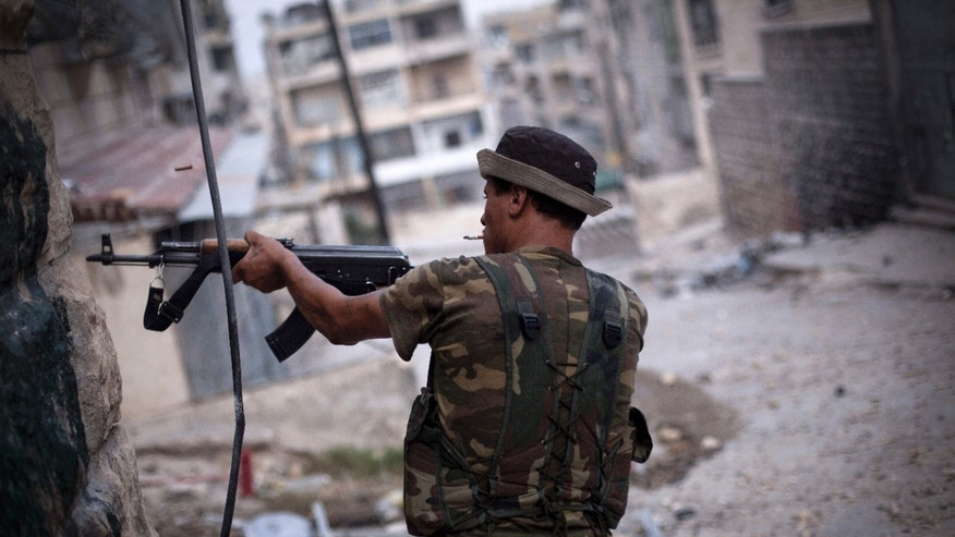 Sept. 11, 2012: In this file photo, A Free Syrian Army fighter fires his weapon at Syrian Army positions in Aleppo, Syria.