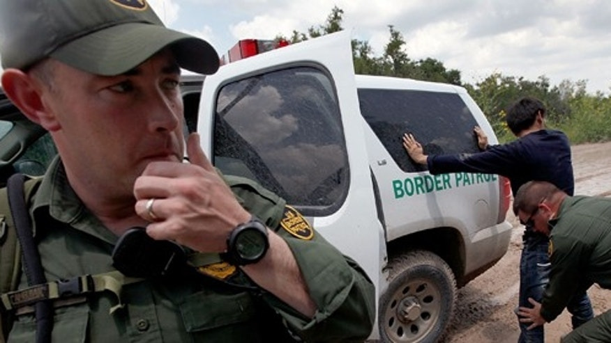 MCALLEN, TX - MAY 27:  A Border Patrol agent searches an undocumented immigrant apprehended near the Mexican border on May 27, 2010 near McAllen, Texas. The man was captured with several other immigrants including two young children in thick brush after crossing the Rio Grande River.  (Photo by Scott Olson/Getty Images)