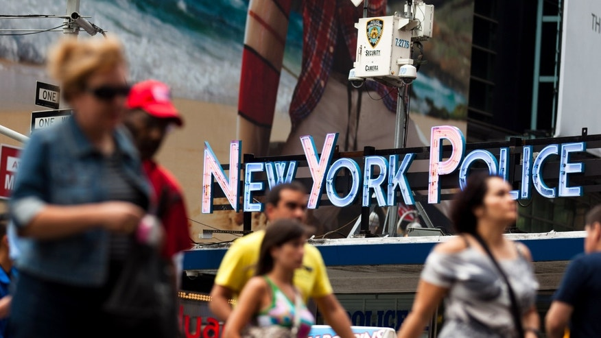 Pedestrians start their morning under the watchful eyes of surveillance cameras in Times Square in New York, Tuesday, Aug. 19, 2011. Since the terrorist attacks of Sept. 11, 2001, the NYPD has become one of the country's most aggressive domestic intelligence agencies, targets ethnic communities in ways that would run afoul of civil liberties rules if practiced by the federal government.  (AP Photo/John Minchillo)