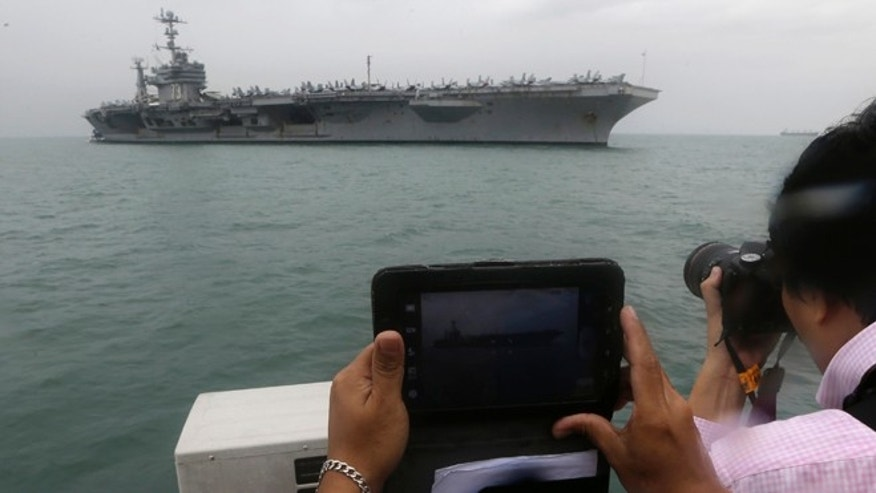 Oct. 25, 2012: Journalists take photos of the U.S. Navy aircraft carrier USS George Washington off Manila Bay in Manila, Philippines.