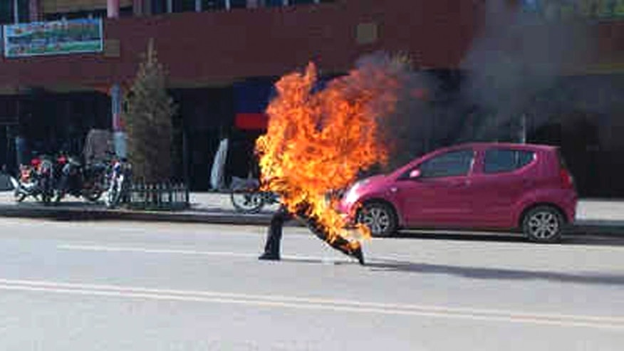 Oct 23, 2012 - Dorje Rinchen, a farmer in his late 50s, runs after setting himself on fire on the main street in Xiahe in northwestern China's Gansu province. (AP/Freetibet.org)