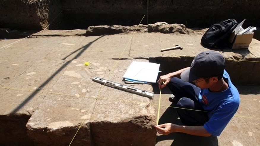Oct. 26, 2012: A Balinese archaeologist measures a stone of ancient temple structure in Denpasar, Bali, Indonesia.