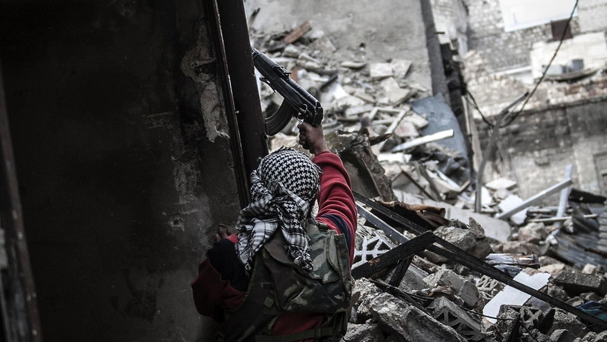 Oct. 25, 2012: In this photo, a Syrian rebel takes cover as he fires at enemy positions in the Karmal Jabl neighborhood, during clashes between rebel fighters and the Syrian army in Aleppo, Syria.