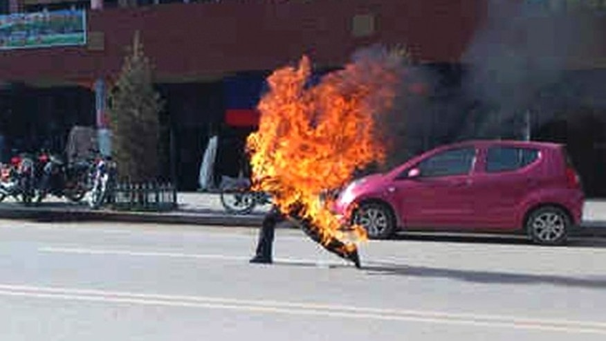 In this photo taken Tuesday, Oct 23, 2012 and released by London-based rights group Freetibet.org, Dorje Rinchen, a farmer in his late 50s, runs after setting himself on fire on the main street in Xiahe in northwestern China's Gansu province.