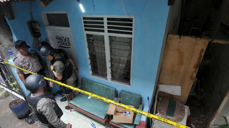 Oct. 27, 2012: Indonesian police officer stand guard outside the house of a suspected terrorist after a raid in Jakarta, Indonesia.